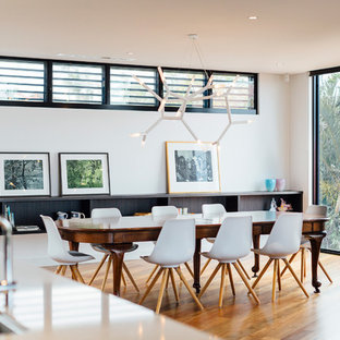 Trendy medium tone wood floor and orange floor dining room photo in Other with white walls