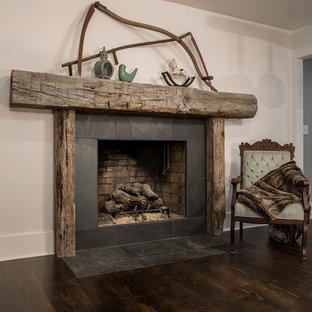 Modelo de comedor rústico con chimenea tradicional y marco de chimenea de madera