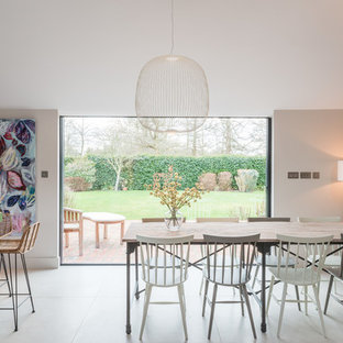 Design ideas for a medium sized farmhouse dining room in Wiltshire with beige walls and white floors.