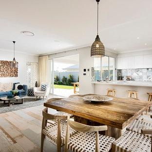 Idée de décoration pour une grande salle à manger ouverte sur la cuisine marine avec un mur beige, aucune cheminée et un sol en bois peint.