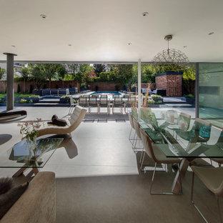 На фото: большая гостиная-столовая в стиле модернизм с белыми стенами, бетонным полом, подвесным камином и серым полом с