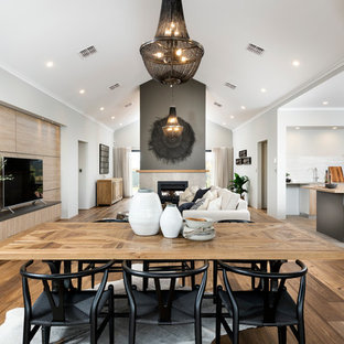 Design ideas for a large transitional open plan dining in Perth with a two-sided fireplace, a tile fireplace surround, white walls and light hardwood floors.