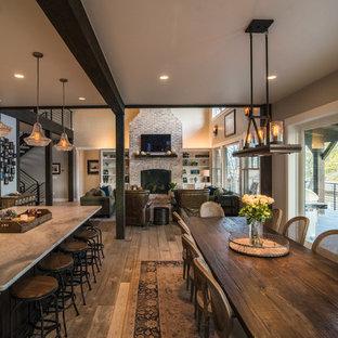 Diseño de comedor rústico, de tamaño medio, abierto, con paredes grises, suelo de madera clara, chimenea tradicional, marco de chimenea de ladrillo y suelo beige