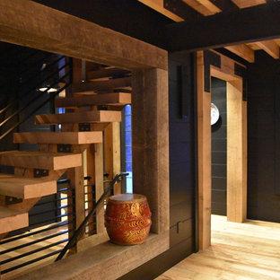 Imagen de comedor de cocina urbano con paredes negras, suelo de madera en tonos medios, chimenea de doble cara y marco de chimenea de hormigón