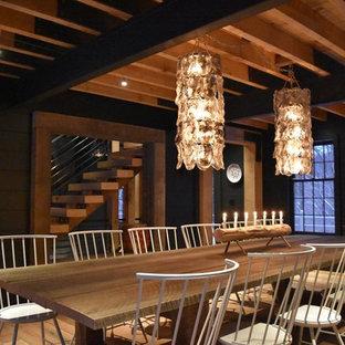 Diseño de comedor de cocina urbano con paredes negras, suelo de madera en tonos medios, chimenea de doble cara y marco de chimenea de hormigón