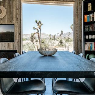 Esempio di una sala da pranzo aperta verso il soggiorno moderna di medie dimensioni con pareti bianche, pavimento in cemento, camino lineare Ribbon, cornice del camino in legno e pavimento grigio