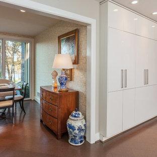 Cette photo montre une salle à manger ouverte sur la cuisine moderne de taille moyenne avec un mur multicolore, un sol en liège et aucune cheminée.