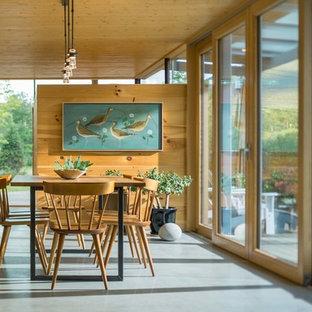Inspiration för mellanstora moderna matplatser med öppen planlösning, med vita väggar, betonggolv, en öppen vedspis, grått golv och en spiselkrans i metall
