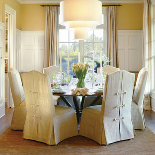 This is an example of a traditional dining room in Portland with yellow walls and dark hardwood flooring.