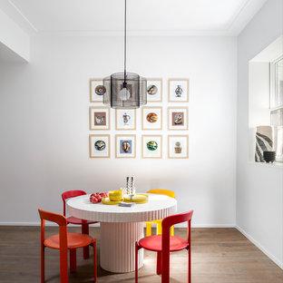 ニューヨークの大きいコンテンポラリースタイルのおしゃれなダイニングキッチン (白い壁、ラミネートの床、暖炉なし、茶色い床) の写真