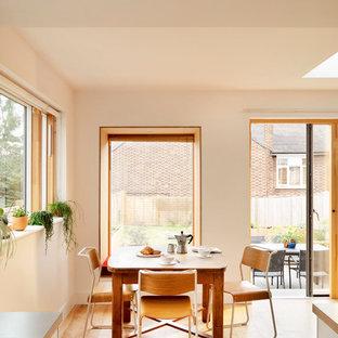 Inspiration för stora minimalistiska matplatser med öppen planlösning, med vita väggar, bambugolv och gult golv