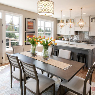 Cette photo montre une salle à manger ouverte sur la cuisine chic avec un mur beige, un sol en bois brun et un sol marron.