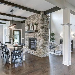Exempel på ett mycket stort lantligt kök med matplats, med grå väggar, mellanmörkt trägolv, en dubbelsidig öppen spis och en spiselkrans i sten
