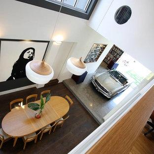 Immagine di una grande sala da pranzo aperta verso la cucina minimal con pareti marroni, pavimento in cemento, camino bifacciale, cornice del camino in cemento e pavimento grigio
