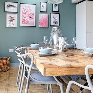 Foto di una sala da pranzo nordica con pareti verdi, parquet chiaro e pavimento beige