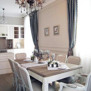 Cette photo montre une salle à manger ouverte sur la cuisine éclectique de taille moyenne avec un mur beige et un sol en bois brun.