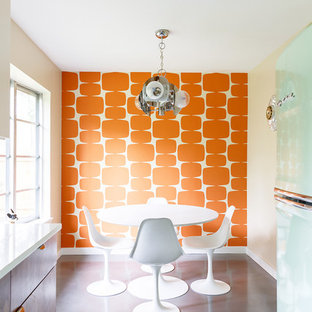 Idee per una sala da pranzo aperta verso la cucina moderna con pavimento in cemento, pareti arancioni, nessun camino e pavimento grigio