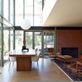 Immagine di una sala da pranzo minimalista con cornice del camino in mattoni e pavimento in legno massello medio