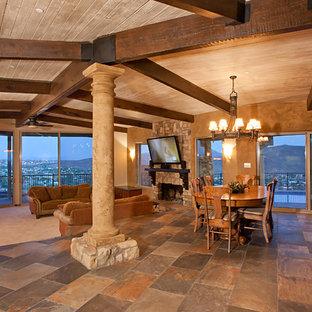 Ejemplo de comedor de cocina clásico, grande, con paredes beige, suelo de pizarra, chimenea tradicional y marco de chimenea de piedra