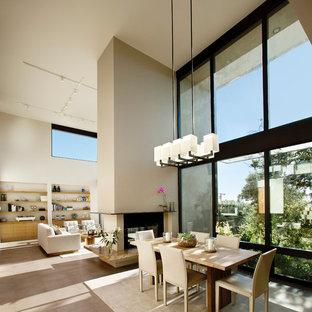 Imagen de comedor contemporáneo, abierto, con paredes beige y chimenea de doble cara
