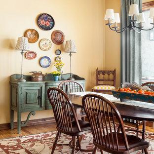 Exemple d'une salle à manger sud-ouest américain avec un mur jaune, un sol en bois brun et un sol marron.