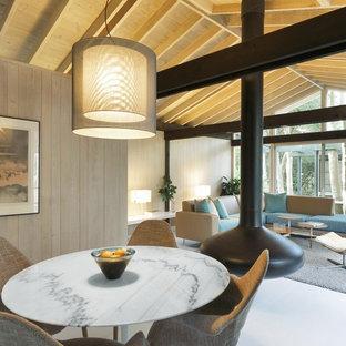 Immagine di una sala da pranzo minimalista con camino sospeso