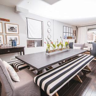 Immagine di una piccola sala da pranzo aperta verso la cucina country con pareti grigie, parquet scuro, camino classico, cornice del camino in legno e pavimento marrone