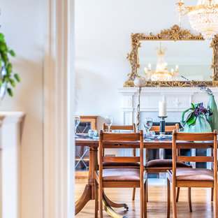 Design ideas for a classic enclosed dining room in London with white walls, medium hardwood flooring, a standard fireplace and brown floors.