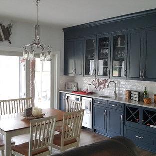 Imagen de comedor de estilo americano, de tamaño medio, abierto, con paredes grises, suelo laminado y suelo marrón