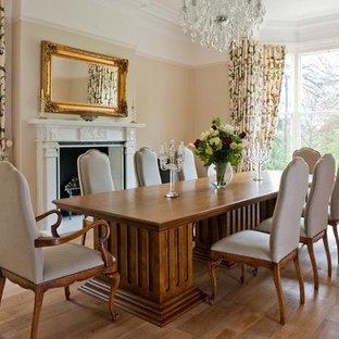 Foto di una sala da pranzo aperta verso la cucina country di medie dimensioni con pareti beige, parquet chiaro, camino sospeso, cornice del camino in intonaco e pavimento beige