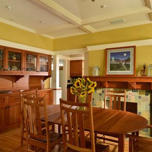 Imagen de comedor de estilo americano con paredes amarillas, suelo de madera en tonos medios, chimenea tradicional y marco de chimenea de baldosas y/o azulejos