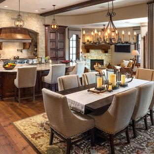 Cette image montre une salle à manger ouverte sur le salon traditionnelle avec un mur beige, un sol en bois brun et un sol orange.