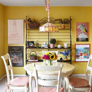 Ejemplo de comedor de cocina clásico con paredes amarillas y moqueta
