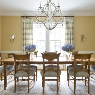 Foto di una sala da pranzo tradizionale con pareti gialle e pavimento in legno massello medio