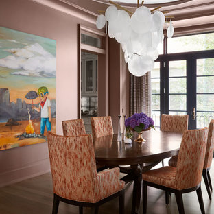 Example of a classic medium tone wood floor and brown floor enclosed dining room design in Chicago with pink walls