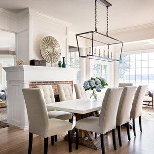 На фото: гостиная-столовая в классическом стиле с паркетным полом среднего тона, белыми стенами, двусторонним камином и фасадом камина из кирпича