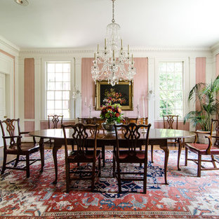 Example of a classic medium tone wood floor dining room design in Atlanta with pink walls and a standard fireplace