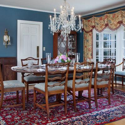 Large elegant medium tone wood floor enclosed dining room photo in Orlando with blue walls