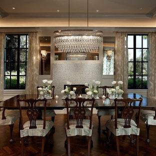 Immagine di una grande sala da pranzo classica chiusa con pareti bianche, parquet scuro, camino classico e cornice del camino piastrellata