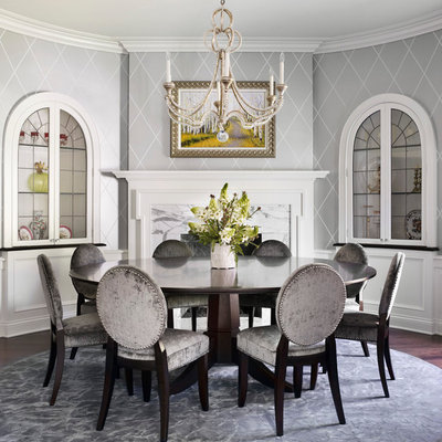 Example of a classic dark wood floor dining room design in Chicago with gray walls, a stone fireplace and a standard fireplace