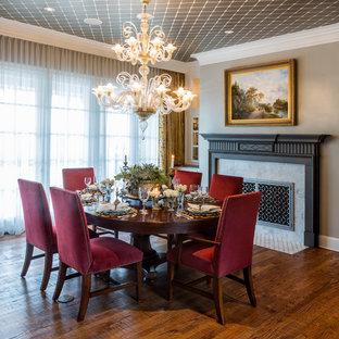 Immagine di una grande sala da pranzo chic chiusa con pareti grigie, pavimento in legno massello medio, camino classico, cornice del camino in pietra e pavimento marrone