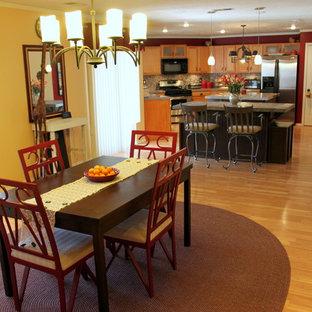 Idee per una sala da pranzo aperta verso la cucina minimal di medie dimensioni con pareti gialle, pavimento in laminato, camino classico e cornice del camino in pietra