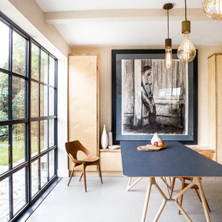 This is an example of a scandinavian dining room in Oxfordshire with no fireplace and grey floors.
