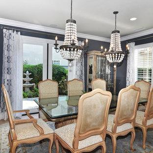 На фото: большая отдельная столовая в стиле современная классика с черными стенами, полом из травертина и коричневым полом без камина с
