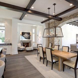 Modelo de comedor tradicional renovado, grande, abierto, con paredes blancas, suelo de madera oscura, chimenea tradicional, marco de chimenea de hormigón y suelo blanco