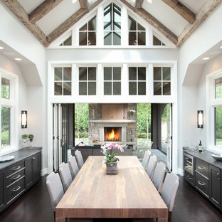 Example of a large transitional dark wood floor and brown floor kitchen/dining room combo design in Minneapolis with white walls, a standard fireplace and a stone fireplace