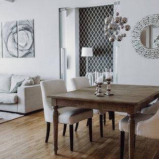 Medium sized traditional open plan dining room in London with white walls and medium hardwood flooring.