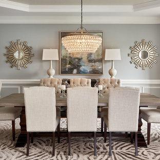 Réalisation d'une salle à manger tradition avec un mur gris et une cheminée standard.