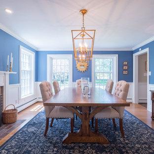 Imagen de comedor tradicional, de tamaño medio, cerrado, con paredes azules, suelo de madera en tonos medios, chimenea tradicional, marco de chimenea de madera y suelo marrón