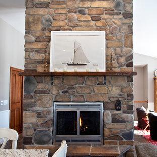 Idee per una sala da pranzo aperta verso il soggiorno american style di medie dimensioni con pareti grigie, pavimento in ardesia, camino classico, cornice del camino in pietra e pavimento marrone